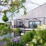 Rodinný dom s prírodným kúpacím jazierkom a okrasnými záhonmi.