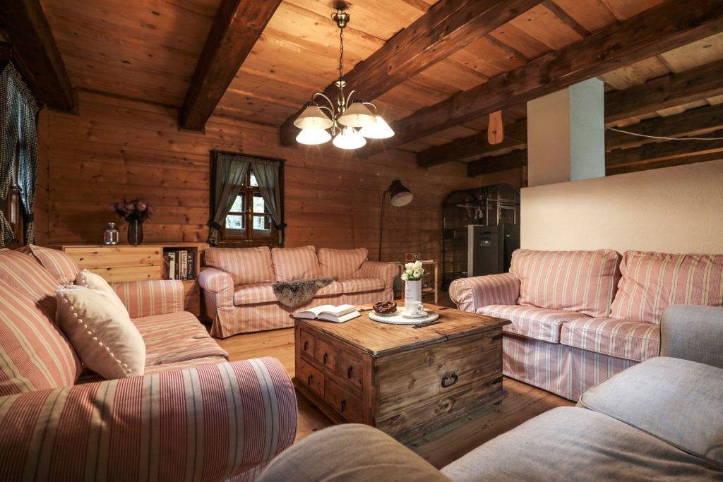 Obývačka v drevenici vo vidieckom štýle s páskovanou sedacou súpravou a truhlicovým stolíkom