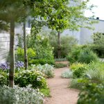 Záhrada s mlatovými chodníkmi a voľne prerastajúcimi trvalkovými výsadbami