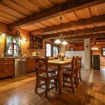 Kuchyňa v drevenici prepojená s obývačkou, obe miestnosti zariadenie vo vidieckom štýle.