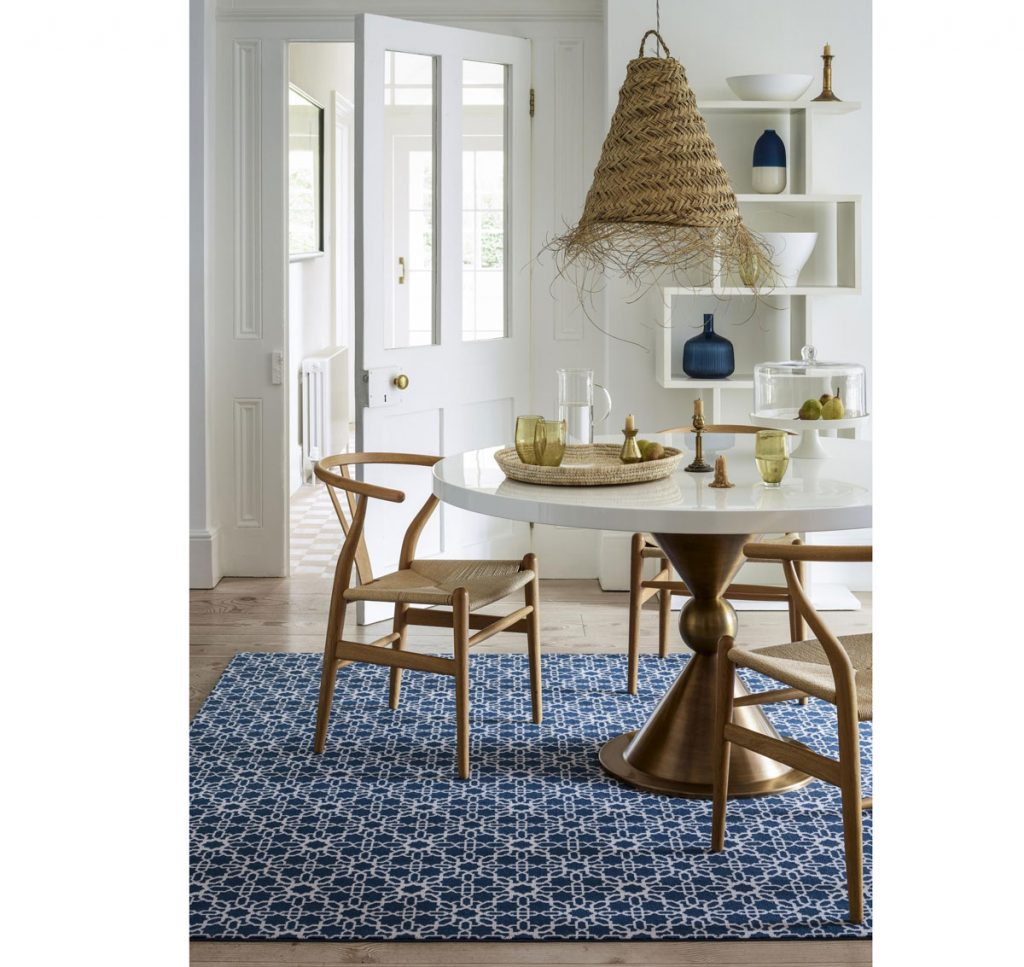 Retro interiér v štýle 60. rokov s dizajnovými drevenými stoličkami, okrúhlym stolom na mosadznej nohe, prírodným pleteným svietidlom a vzorovaným kobercom.