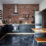 Kuchyňa v industriálnom štýle s tehlovou stenou, čiernou kuchynskou linkou bez tradičných horných políc, tmavou podlahou a záhradnou lavicou slúžiacou ako jedálenský stôl.