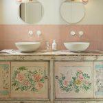 Kúpeľňa s vintage skrinkou so vzorom ruží, dvoma umývadlami a okrúhlymi zrkadlami.