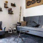 Obývačka v industriálnom štýle s motorkárskymi prvkami, s tmavou sedacou súpravou, tmavou podlahou, poličkami na dekorácie a ručne vyrobeným stolom z brzdových kotúčov.