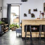 Industriálny interiér s motorkárskymi a prírodnými prvkami, v ktorom je kuchyňa od obývačky oddelená barovým pultom