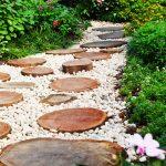 Záhradný chodníček z bieleho štrku s guľatinovými nášľapnými plochami.
