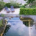 Prírodné kúpacie jazierko s drevenou terasou s ležadlami, štrkovým brehom, mlatovými chodníkmi a kvetinovými záhonmi.