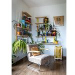 Čitateľský kútik so svetlým retro kreslom, drevenou otvorenou knižnicou s knihami a rastlinami.