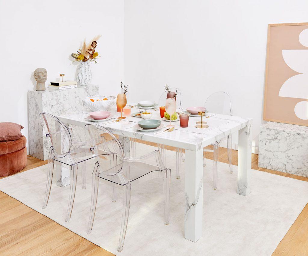 Interiér s mramorovým stolom a priehľadnými stoličkami.