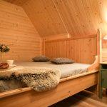 Spálňa v podkroví drevenice zariadená vo vidieckom štýle s drevenou posteľou a dreveným obkladom na stenách.