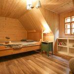 Spálňa v podkroví drevenice zariadená na vidiecky štýl dreveným nábytkom, so stenami obloženými drevom.