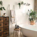 Kúpeľňa v prírodnom duchu so samostatne stojacou vaňou, rebríkom a komodou.