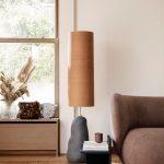 Prírodne ladený interiér s pohovkou a stojacou lampu.
