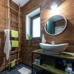 Kúpeľňa s dreveným obkladom, okrúhlym zrkadlom, ktorý má namiesto rámu lano, so závesným rebríkom a drevenou policou s kovovou konštrukciou s úložnými krabicami vyrobenými z debničiek od paradajok.