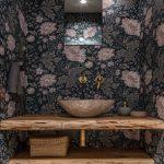 Kúpelňa s dreveným nábytkom, kamenným umývadlom a vzorovanou kvetinovou tapetou