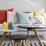 Pohovka so vzorovanými a farebnými vankúšmi a okrúhle retro stolíky s vázami.