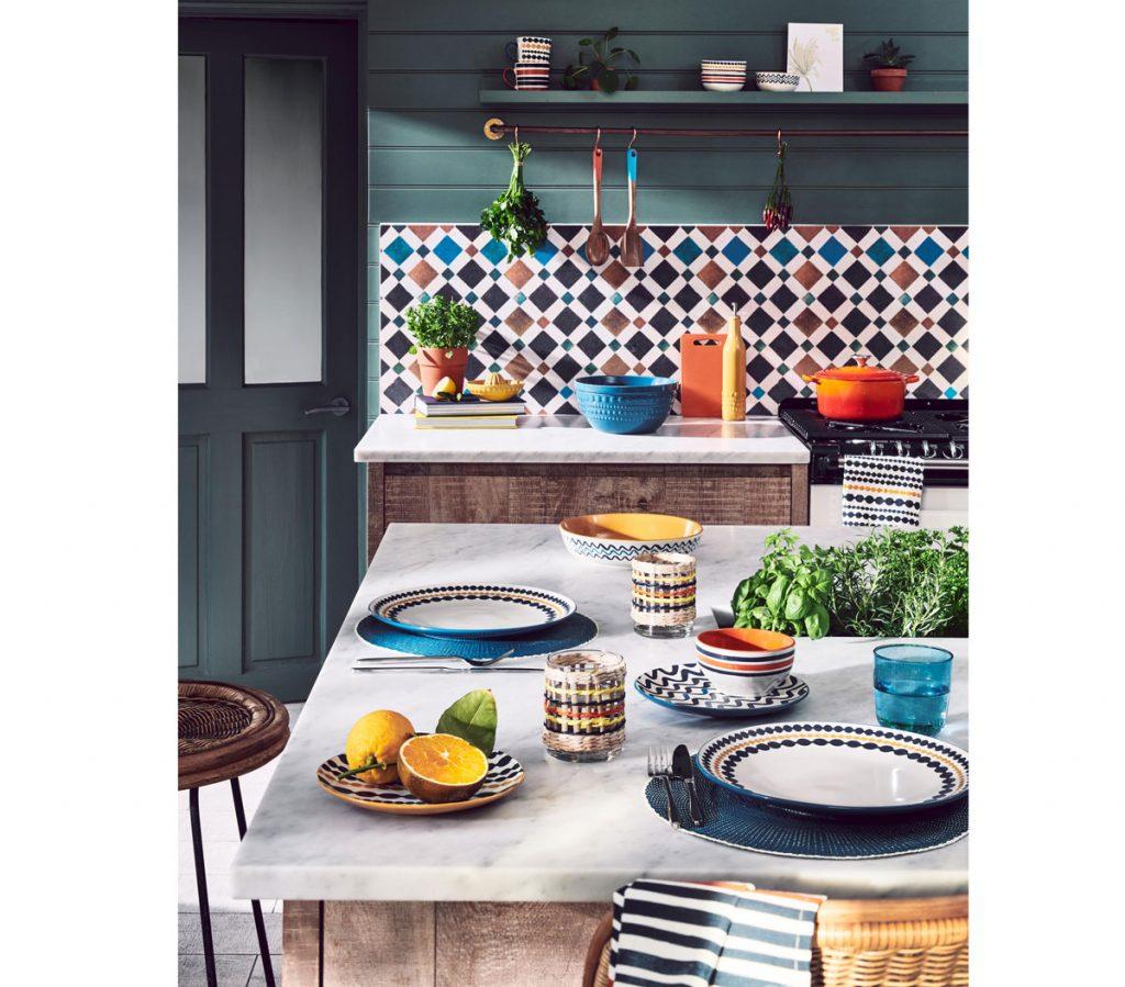 Kuchyňa v retro štýle 60. rokov so vzorovanou zástenou, drevenou kuchynskou zostavou a vzorovanými jedálenskými riadmi.