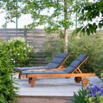 Záhrada s menšou terasou s drevenými ležadlami.