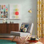 Retro obývačka so sivým dreveným kreslom, vzorovanými textíliami, tmavohnedou komodou a abstraktnými obrazmi.