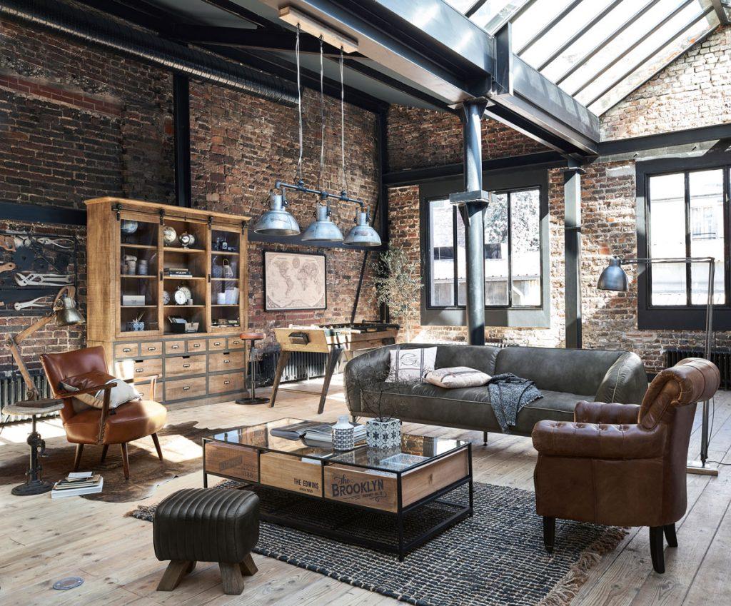 Industriálna obývačka s koženou pohovkou a kreslami, stolíkom, skriňou, kovovým lustrom a tehlovými stenami.