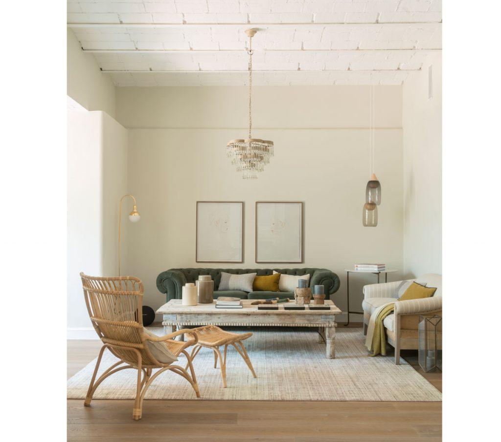 Obývačka s čalúnenou pohovkou, dreveným vintage stolom a ratanovým kreslom