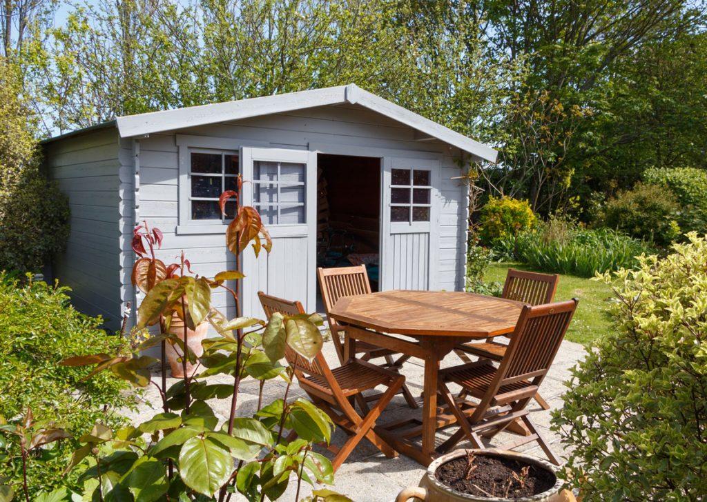 Ochrana exteriérového dreva: záhrada s dreveným záhradným domčekom a nábytkom