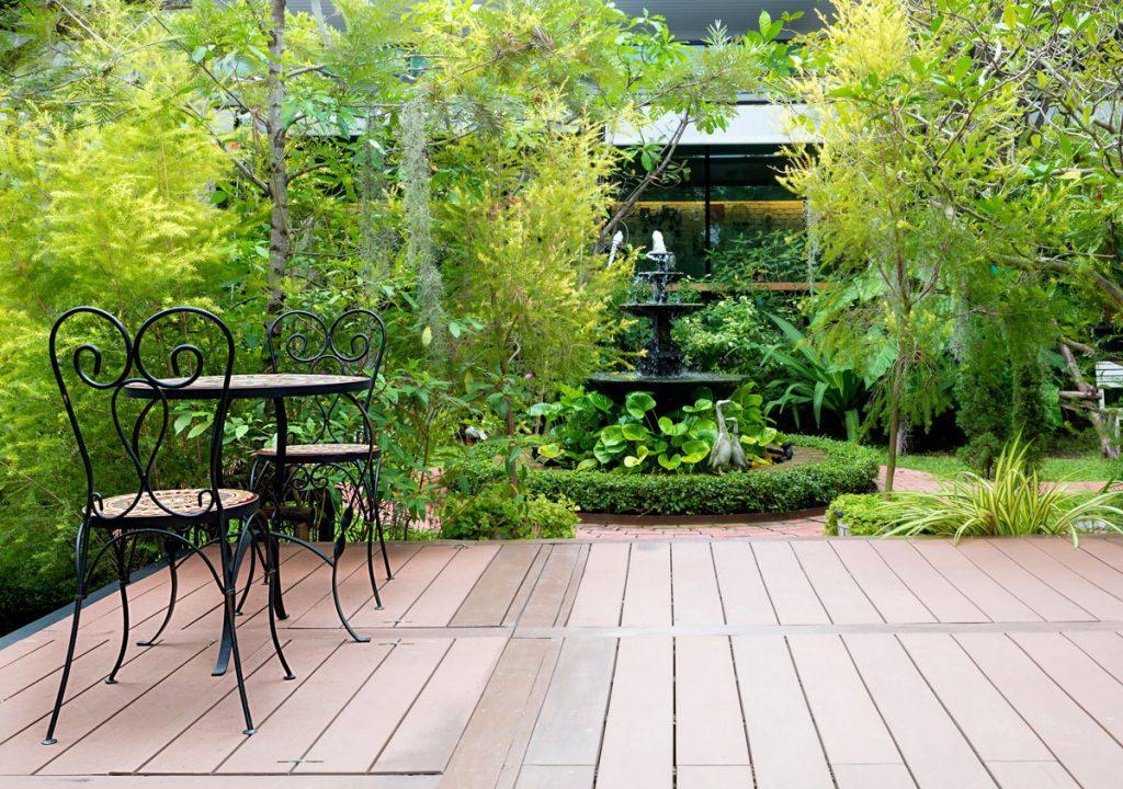 Záhrada s terasou, stolíkom a stoličkami, fontánou a okrasnými rastlinami