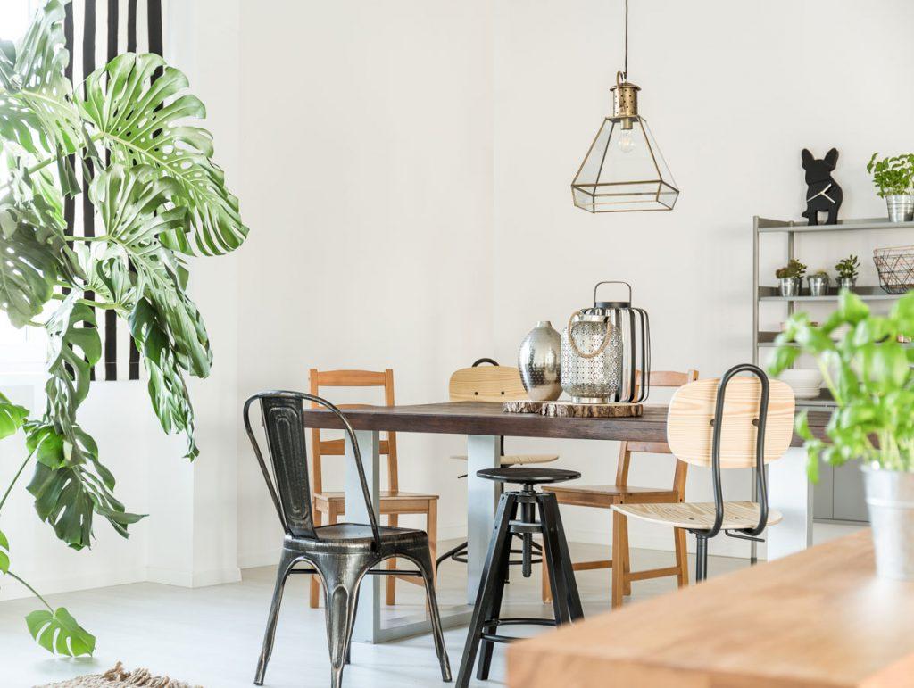 Kombinovanie materiálov v interiéri: jedáleň v industriálnom štýle s kovovými a drevenými stoličkami, lampou zo skla a striebornými doplnkami