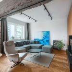 Industriálny interiér obývačky spojenej s kuchyňou s predeľovacím prvkom v podobe stropného betónu, na ktorom je uchytený posuvný regál.