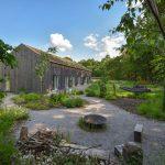 Rodinný dom so zelenou strechou a prírodnou záhradou s otvoreným ohniskom, trvalkovými záhonmi, stromami a hojdacou sieťou.