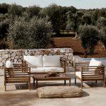 Posedenie na terase s drevenými lavicami, prestretým stolom a textíliami.