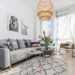 Obývačka v severskom štýle so sivou sedačkou, kovovými stolíkmi, prírodným pleteným kreslom a lustrom a s obrazmi zvierat.