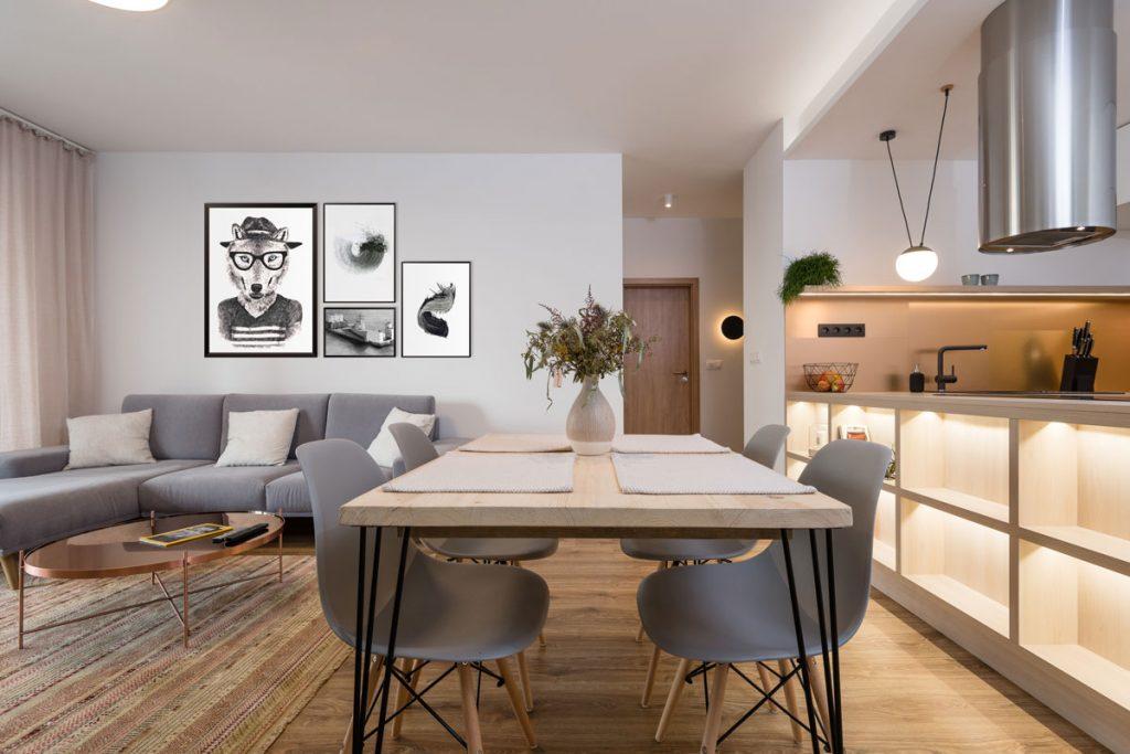 Otvorený priestor obývačky a kuchyne, v zemitých odtieňoch, so sivou sedačkou, jedálenským stolom a sivými stoličkami a s ostrovčekom so zabudovanými svetlami.