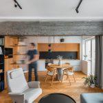 Otvorený interiér obývačky a kuchyne s deliacim prvkom v podobe stropného betónového hranolu s koľajničkou pre posúvanie regálu.