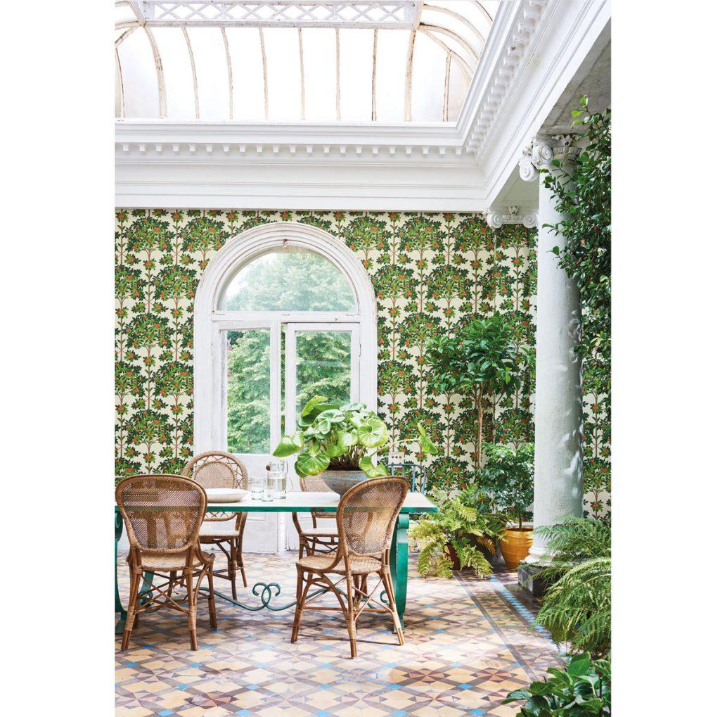 Interiér jedálne zariadený v španielskom štýle s výraznými florálnymi tapetami, vzorovanou dlažbou a stĺpom.