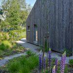 Detail drevostavby s prírodnou záhradou navrhnutou podľa hygge filozofie.