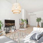 Obývačka zariadená v severskom štýle s otvoreným priestorom do kuchyne a chodby.