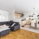 Otvorený priestor obývačky s kuchyňou v škandinávskom minimalistickom štýle s rohovou sedačkou, kuchynskou zostavou vo svetlom dreve a bielym jedálenským stolom a stoličkami.