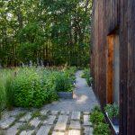 Drevostavba s prírodnou záhradou navrhnutou podľa hygge filozofie, s vyvýšenými bylinkovými záhonmi a chodníkom z dubových fošní