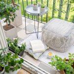 Balkón s pufom, stolíkom a izbovými rastlinami.