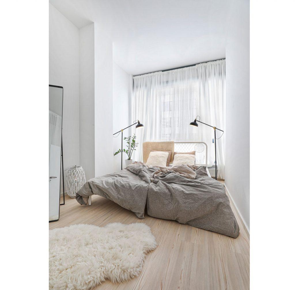 Spálňa v prírodnom štýle s kovovou posteľou a ovčou kožušinou