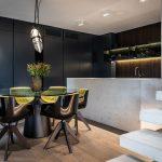 extravagantný jedálenský stôl s čiernymi lesklými stoličkami a atypickým svietidlom