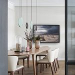 Elegantná jedáleň s drevenou podlahou, dreveným oválnym stolom a koženými smotanovými stoličkami a atypickým lustrom