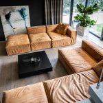 Obývačka v minimalistickom duchu zariadená modulárnou koženou sedačkou, štvorcovým čiernym stolíkom, kvetinou a moderným obrazom opretým o stenu