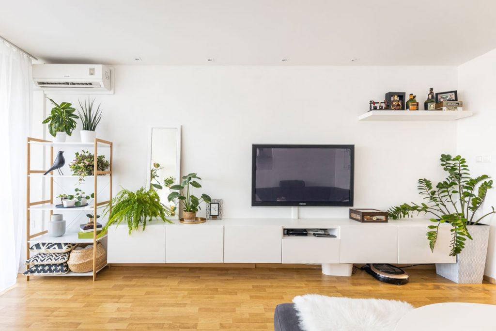 Obývačka v minimalistickom štýle s dreveným regálom s dekoráciami a kvetinami a závesnou skrinkou pozdĺž steny
