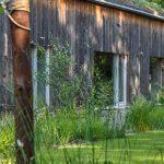 Drevostavba rodinného domu s prírodnou záhradou citlivo zasadenými medzi okolité lesy.