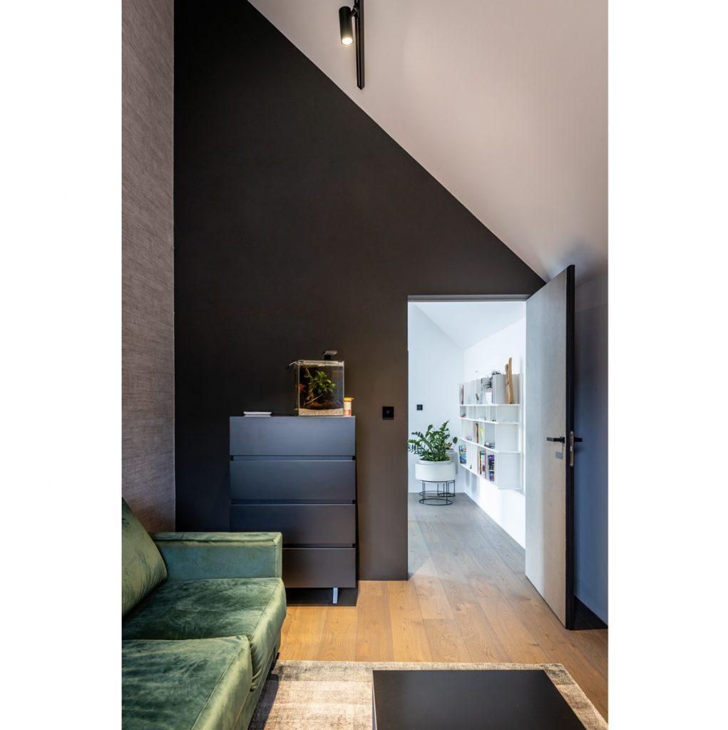 Interiér s tmavozelenou zamatovou sedačkou, čiernou skrinkou a stenami tiež v odtieňoch čiernej