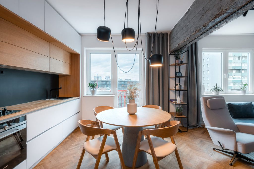 industriálna kuchyňa s minimalistickou linkou, jedálenským stolom a nosným betónovým prekladom, na ktorom je umiestnený posuvný regál