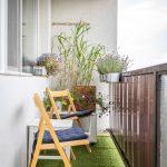 lodžia so zeleným kobercom, stoličkami a stolíkom a okrasnými kvetinami
