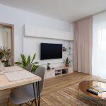Obývačka v severskom štýle v zemitých odtieňoch, pohľad na TV stenu s niekoľkými úrovňami hĺbky